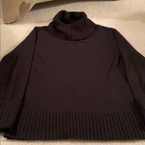 Black turtleneck with ribbed cuffs and neck